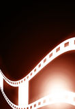 Glowing filmstrip. Glowing red filmstrip on a dark background Royalty Free Stock Photo