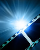 Glowing filmstrip. Glowing film strip on a blue background Stock Image