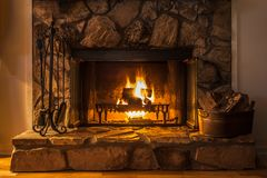 A glowing fire on a winter`s night. A glowing fire in the stone fireplace to warm a chilly night stock photos