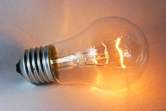 Glowing flashing light bulb lamp laying. On white background Royalty Free Stock Images