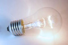 Glowing flashing light bulb lamp laying. On white background Royalty Free Stock Photos