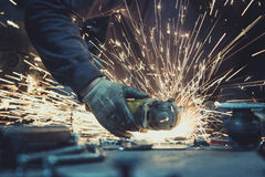 Glowing flow of sparks made by sawing a piece of steel with an angle grinder on a work surface Stock Image