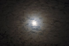 Glowing full moon surrounded by layers of moody soft clouds lit stock images
