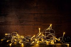 Glowing garland in dark. Composed lights of garland burning in dark on wooden background Stock Photo