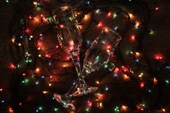 Glowing garland glass. Glowing garland lights dark background wire two glasses Royalty Free Stock Photo