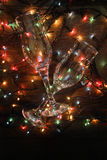 Glowing garland and glasses. Glowing garland lights dark background wire glass Royalty Free Stock Photos