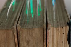 Glowing glass fiber cables connected with old books. Stock Photography