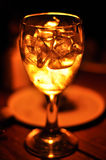 GLowing glass of Ice!. A glass filled with white spirit and ice giving a liquid gold like effect in the glass Royalty Free Stock Photography