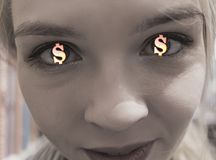 Glowing gold dollar signs in eyes of a young girl. the concept of chasing money and greed