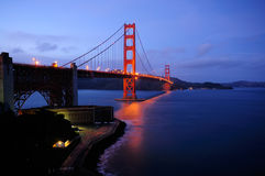 Glowing Golden Gate Bridge and Fort Point. Golden Gate Bridge and Fort Point overlook glow in the dusk after a winter storm - landscape orientation Royalty Free Stock Photography