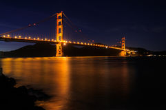 Glowing Golden Gate Bridge and star trails. Golden Gate Bridge as seen from Fort Point overlook is glowing in the night with star trails in the sky behind it Royalty Free Stock Photos