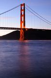 Glowing Golden Gate Bridge tower at sunset Stock Images