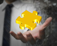 Glowing golden jigsaw puzzle in businessman hand Stock Image