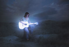 Glowing guitar at night. Woman playing a glowing guitar at night Stock Images
