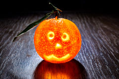Glowing halloween mandarin on wooden table in mystique light with orange shadows Stock Photo