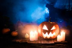 Glowing Halloween pumpkin with scarecrows on the field Stock Image