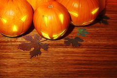 Glowing Halloween pumpkins border. Warm candle light, autumn holiday background, traditional jack-o-lantern over wood, night party decoration Royalty Free Stock Photo