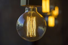 Glowing hanging spherical retro vintage edison incandescent bulbs against a blurred dark wall and other lamps. A glowing hanging spherical retro vintage edison royalty free stock photography