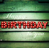 Glowing Happy Birthday on wooden background Stock Photography