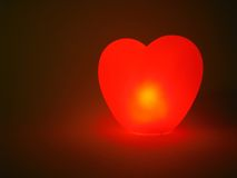 Glowing heart. On dark red background Royalty Free Stock Photography