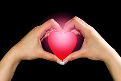 Glowing heart in hands Stock Image