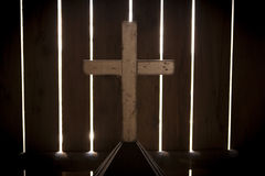 Glowing hidden cross. Picture of a white wooden cross hidden in an abandoned elementary school. It is in a dark room and the cross is lightly lit and it seems to Stock Image