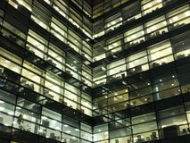 Glowing illuminated windows in a large modern geometric city office building at night showing work spaces stock photos
