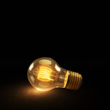Glowing Incandescent Light Bulb on a Dark Background Royalty Free Stock Image