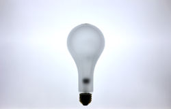 Glowing Incandescent Lightbulb. An incandescent lightbulb lit against a backlight Royalty Free Stock Image