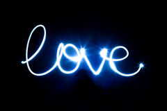 Glowing inscription LOVE on a black Royalty Free Stock Photos