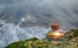 Glowing inside magic bottle on the rock by the ocean wave Stock Photography