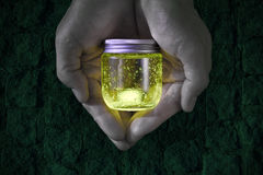 Glowing jar in the hands Stock Image