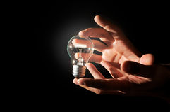 Glowing lamp. Holding a normal light bulb in the hands Stock Image