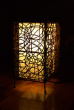 Glowing lamp. A decorative lamp with a design made of wicker glowing on a wooden tabletop Stock Photography