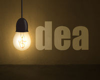 Glowing lamp with money symbol and idea word on concrete wall in Stock Photography