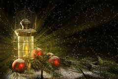 Glowing Lantern Christmas Night. An old brass oil lamp casting warm light glow onto rustic wood porch decorated with pine boughs and red ornaments on snowy