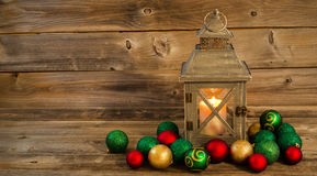 Glowing Lantern with Christmas Ornaments on Rustic Wood. Horizontal front view of an old Asian design lantern and white candle glowing brightly inside with Stock Photos
