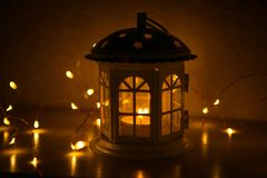 Glowing lantern in the shape of a house with Windows lit yellow. royalty free stock photos