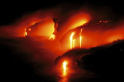 Glowing Lava Flow in Hawaii. Lava from Kileauea Volcano flowing into the sea at night, Hawaii Volcanoes NP, Island of Hawaii, Hawaii Stock Photo