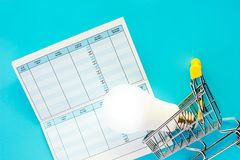 Glowing LED light bulb with mini shopping cart or trolley and sa. Vings book on blue background for energy savings and planning concept royalty free stock photos