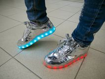 Glowing LED sneakers on the feet of a man stock image