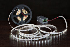 Glowing LED Strip Light on coil, close to  power supply, on blac Royalty Free Stock Photo