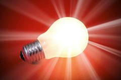 Glowing light bulb. Turned on over a orange background Stock Image