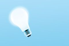 Glowing light bulb. On a light blue background royalty free stock photo