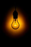 Glowing Light Bulb. Light bulb in darkness, with orange glow royalty free stock photography