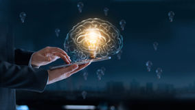 Glowing light bulb in brain over labtop of businessman. Among the others that not bright, it`s symbolic of creative and bright idea or leadership, innovation royalty free stock image