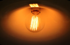 Glowing light bulb. Light bulb in darkness, with orange glow Stock Photo