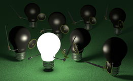 Glowing light bulb fighting against many black ones on green Stock Image
