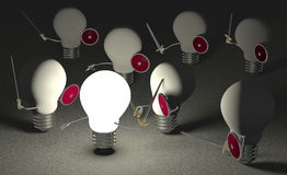 Glowing light bulb fighting against many switched off ones on gray Royalty Free Stock Photos