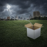 Glowing light bulb float over box on city, Think outside the box Stock Image